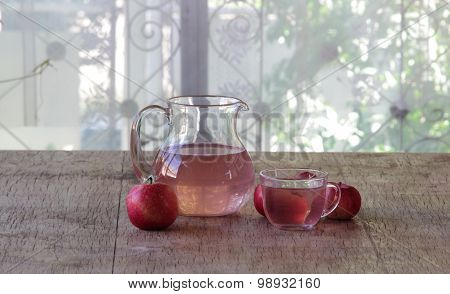 Red Apples And Apple Compote In A Transparent Jug On A Wooden Table