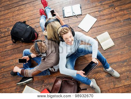 Group of students using smartphones and tablet in headphones listening to the music and leaning on each other on wooden floor having notebooks and bags around them.