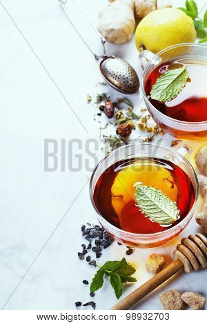 Tea with mint, ginger and lemon on marble background