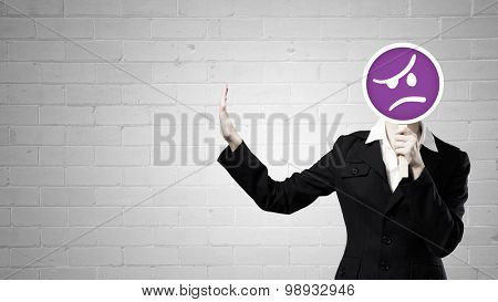 Businesswoman hiding her face behind mask and showing stop gesture