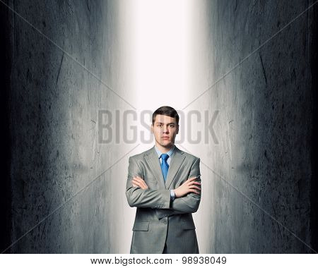 Young confident businessman with hands crossed on chest between two walls