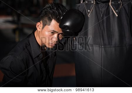 Tired businessman in Boxing Gloves with punching bag at gym