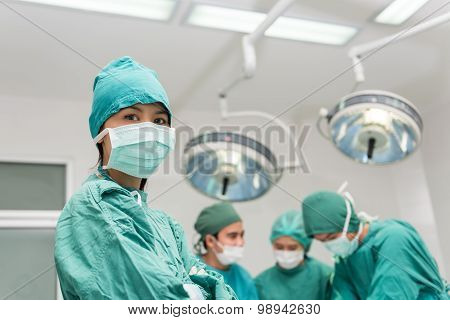 Female doctor with surgical team on background.