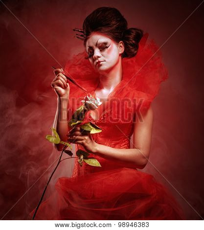 Red Queen. Woman With Creative Make-up In Fluffy Red Dress With A White Rose And Paintbrush Posing I