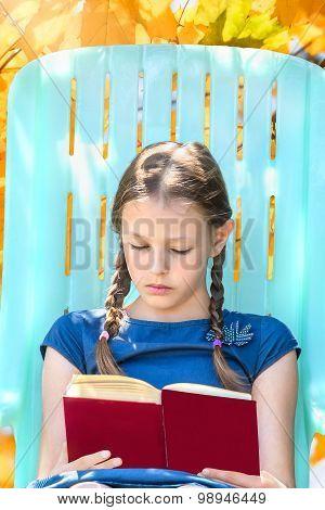 Girl Reading A Book In Autumn Garden