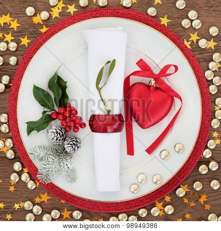 Christmas holiday dinner place setting with plate, napkin, heart bauble decoration and winter flora over oak table background.