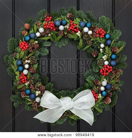 Christmas wreath with white bow, bauble decorations, holly, mistletoe, pine cones and blue spruce fir over dark oak background.