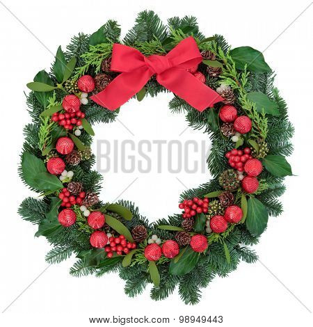 Christmas wreath with red bauble decorations and bow, holly, ivy, mistletoe and winter greenery over white background.