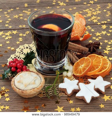 Christmas mulled wine with gingerbread biscuits, mince pie, spices, fruit, holly and mistletoe over oak background.