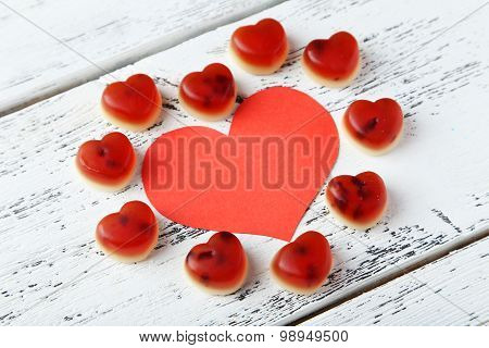 Colorful Jelly Candies With Paper Heart On White Wooden Background