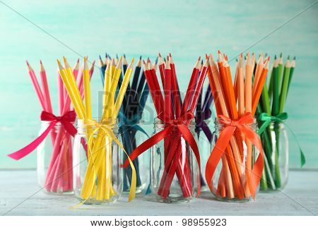 Bright pencils in glass jars on wooden table, on turquoise background