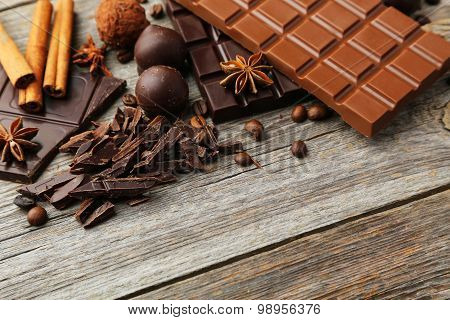 Dark And Milk Chocolate Bar With Coffee Beans And Cinnamon On Grey Wooden Background