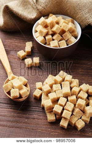 Brown Sugar In Spoon And Bowl On Brown Wooden Background