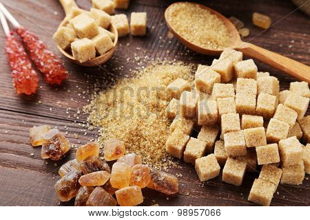 Various Kinds Of Sugar On Brown Wooden Background