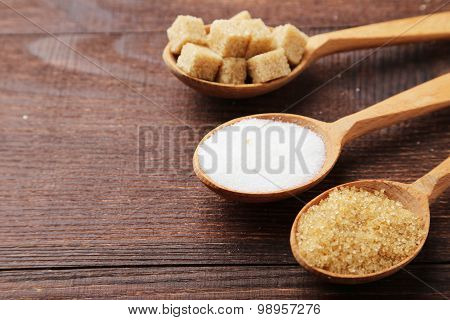 Various Kinds Of Sugar In Spoons On Brown Wooden Background