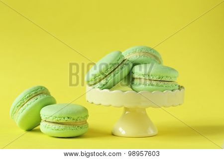 Green Macarons On Yellow Paper Background