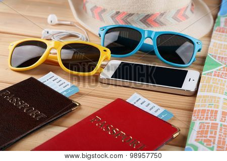 Sunglasses, passports and map, close up, on wooden background. Preparing for travel concept
