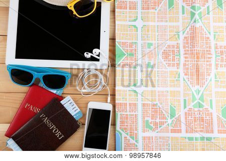Sunglasses, passports, tickets, PC tablet, close up, on wooden background. Preparing for travel concept