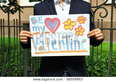 Man holding poster with phrase BE MY VALENTINE, outdoors