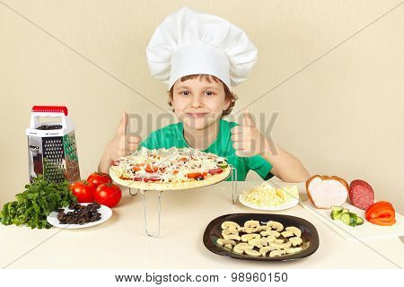 Little funny chef in chefs hat enjoys cooking tasty pizza