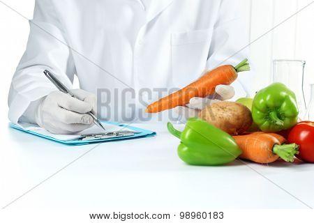 Scientist examines vegetables in laboratory