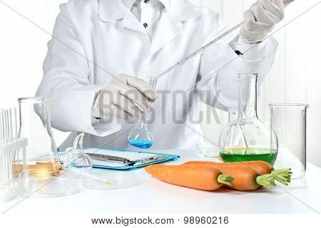 Scientist examines carrots in laboratory