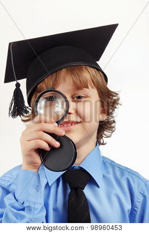 Little smiling professor in academic hat with a magnifying glass on white background