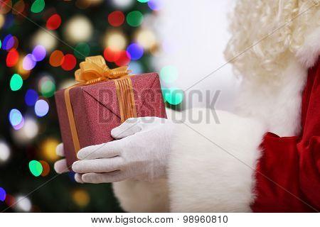 Santa holding gift on Christmas tree background
