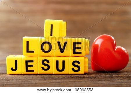 I LOVE JESUS sign illustrated with yellow plastic letters on wooden background