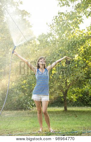 Cheerful Young Woman Spraying Herself With Water On A Hot Summer Day Holding The Hosepipe Above Her