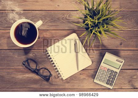 Business analysis concept. Top view workspace with booklet, pen, calculator, glasses and coffee mug. Wooden table background vintage toned.