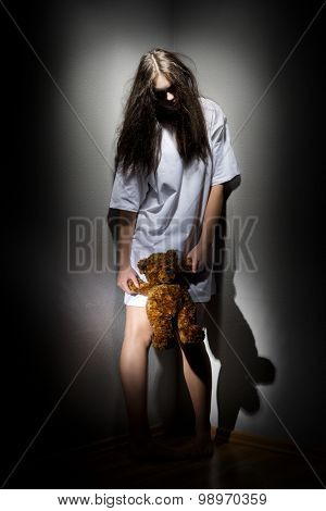 Young zombie girl with teddy bear