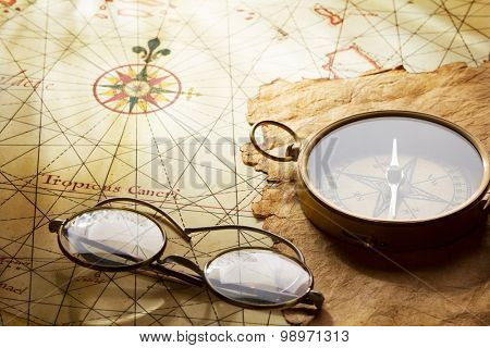 Compass and glasses on antique map. The map of West Indies dated the end of 1600 yy , contains text in latin