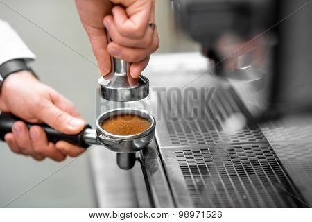 Pressing coffee in the machine holder
