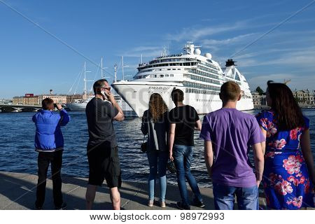 ST. PETERSBURG, RUSSIA - AUGUST 5, 2015: People make photos of cruise liner Seabourn Quest departed from the Neva river. The ship built in 2011 provides luxury cruise for 450 guests