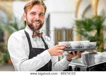 Portrait of barista with coffee cups