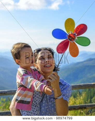 Summer Holidays, Family, Children And People Concept - Happy Mother And Child Girl With Pinwheel Toy