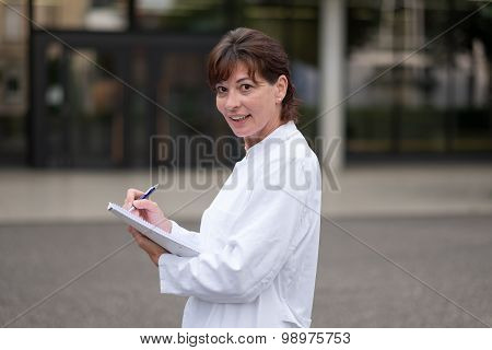 Smiling Doctor Or Nurse Taking Notes