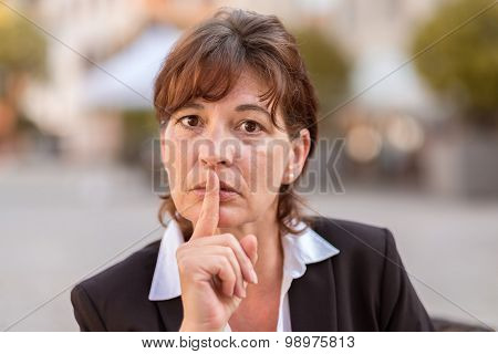 Businesswoman With Her Finger Raised To Her Lips