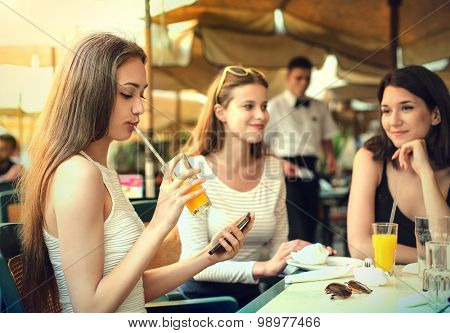 Three girls sitting at a cafe