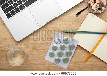 Antivirus set with green pills blister pack and laptop