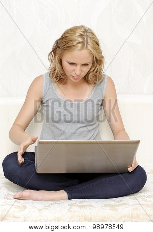 Surprised young woman looking at laptop screen
