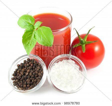 Glass of tomato juice with tomato, basil, pepper and salt