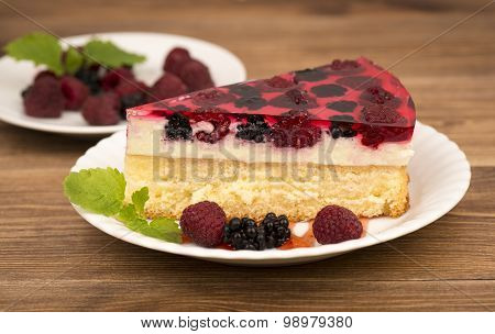 A piece of cheesecake with berries on the plate on the wooden background.