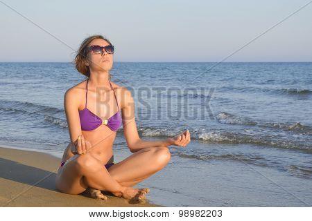 Girl In Bikini Meditating On The Beach