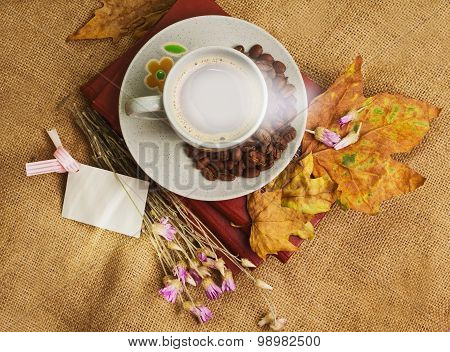 The Cup Of Coffee Lying On The Books With Maple Leaves