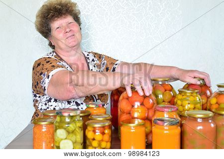 Mature housewife with home canned vegetables