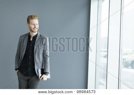 Young Man With Tablet By The Wall
