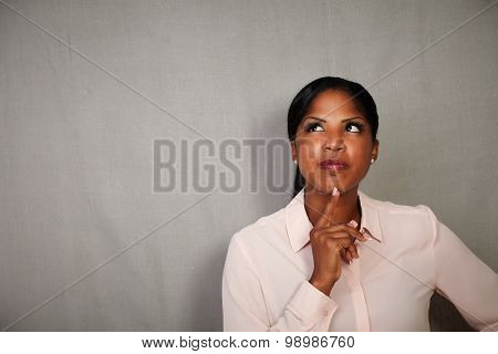 Young Woman Thinking Against Grey Background