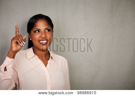 Young Businesswoman Pointing Up While Looking Away